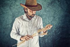 Farmer with cowboy straw hat holding wheat ears Stock Photos