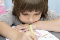 Lonely girl drawing at kindergarten - stock photo