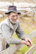 Old shepherd man smoking reflexive near his enclosure - stock photo