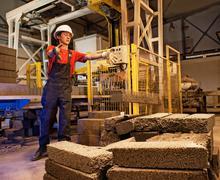 factory worker throwing defective block - stock photo