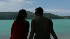 Couple sitting on the waters edge - stock footage