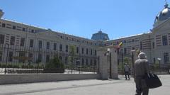 Romania national flag on landmark hospital gate people on street hurrying summer - stock footage