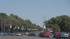 Heavy cars traffic, crowded street beautiful boulevard with green trees on sides Stock Footage