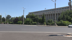 Cars moving in front of Romanian Government building, sunny day out, clear view Stock Footage