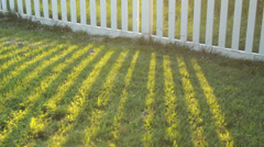 White picket fence casting shadow Stock Footage