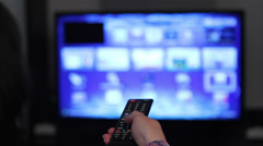 Smart tv and young woman hand pressing remote control - stock footage