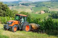 Stock Photo of fields full of vines and red tractor in tuscany