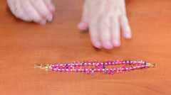 Wearing magenta mother of pearl sticks bracelet Stock Footage