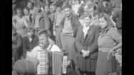 Refugees gathered around a man playing an accordion Stock Footage