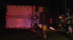 Overturned semi truck and trailer night CU Stock Footage