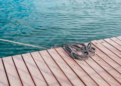 Coiled marine rope on wooden pier Stock Photos