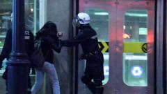 Riot officers pushing girl with camera Stock Footage