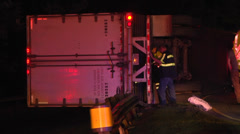 Wrecker personnnel examine overturned semi truck and trailer night Stock Footage