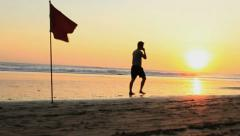 A Man Walks on th Beach at Sunset Speaking on a Cell Phone Stock Footage