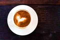 Rusty cup of capuchino coffee in a white cup on wooden background Stock Illustration