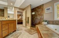 Stock Photo of spacious bathroom with corner bath tub and open shower