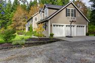 Stock Photo of house exterior. view of three car garage with driveway and basketball court