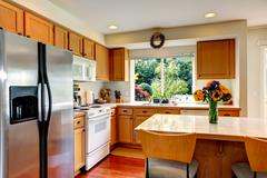 cozy kitchen interior with island and window - stock photo