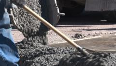 Legs and feet of concrete workers raking fresh mix Stock Footage