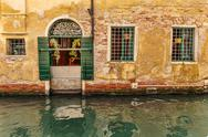 Stock Photo of facade of an old house on a canal in venice, italy