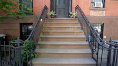 Establishing shot of brownstone building from stairs Stock Footage