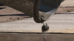 Close up of wet concrete mix dropping from cement mixer chute Stock Footage