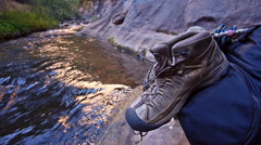 Hiking Boots on Backpack at a Creek in a Wilderness Setting Stock Footage