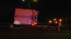 Fireman examines overturned semi truck and trailer night Stock Footage