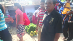 Local man selling plants and women buying by at Hikkaduwa market. Stock Footage
