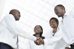 Four african business partners shake hands Stock Photos