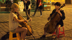 Attractive female street musicians performing cello concert - stock footage