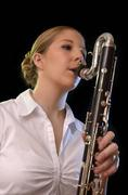 Pretty young woman playing bass clarinet Stock Photos