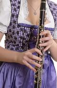 woman in dirndl dress playing clarinet, detail - stock photo