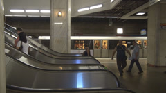 Crowd commuters using stairway, escalators, in subway station train leaving fast Stock Footage