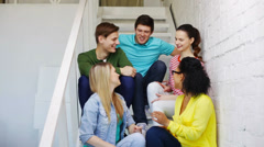 Smiling students sitting on stairs and talking Stock Footage