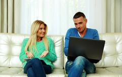 young couple sitting on the sofa and using tablet computer with laptop at hom - stock photo