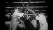 Two workers tightens nut of propeller to aeroplane engine Stock Footage