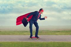 Superhero businessman riding a skateboard Stock Photos