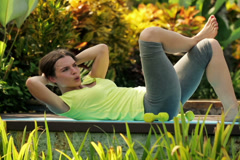 Young attractive woman doing sit-ups exercise in garden NTSC Stock Footage
