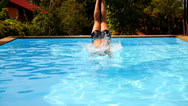 Stock Video Footage of Muscular Man Jumping into the Blue Water in Outdoor Pool near Luxury Resort.
