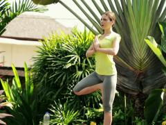 Young woman exercising, doing yoga poses in beautiful garden NTSC Stock Footage