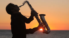 The silhouette of a musician playing saxophone on the seacoast at sunset Stock Footage
