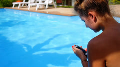 Young Woman Texting on the Phone while Relaxing in Private Pool near Luxury Stock Footage