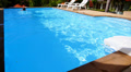 Man Swims Back in Private Outdoor Swimming Pool near Luxury Villa. Footage