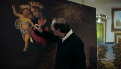 Elderly artist paints a picture. Madonna and child Stock Footage