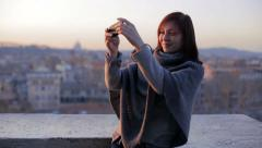 Woman taking self portrait in the terrace with Rome on background Stock Footage