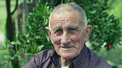 Smiling old countryman looks into the camera sitting on a chair: wrinkled Stock Footage