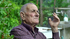 smoking old man sitting in a green countryside context: relaxing, resting - stock footage