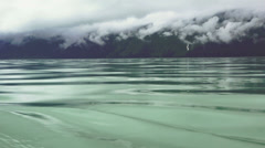 Hovering In Motion Inches over The Water with Scenic Cloudy Mountains. Stock Footage