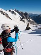 mountaineer taking picture with a camera in the mountains. - stock photo